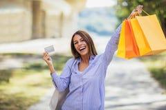 De holding van de vrouw het winkelen zakken en een creditcard stock afbeeldingen