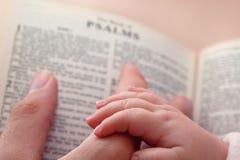 De Vinger van Dadâs van de Holding van de baby op Bijbel Royalty-vrije Stock Afbeeldingen