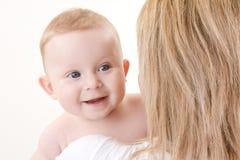 De holdings glimlachende baby van de moeder stock fotografie