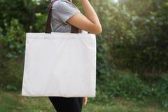 de holdings katoenen van de vrouwenhand zak op groene achtergrond Eco royalty-vrije stock afbeelding