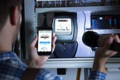 De Holdings Mobiele Telefoon die van de mensen` s Hand Elektrische Meterlezing tonen royalty-vrije stock afbeeldingen