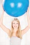 De holdings pilates bal van de vrouw over haar hoofd Stock Afbeeldingen