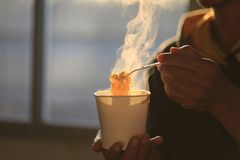 De holdings plastic vork van de mensenhand van onmiddellijke noedels met rook die op de achtergrond van de huiszonsondergang, de  royalty-vrije stock fotografie