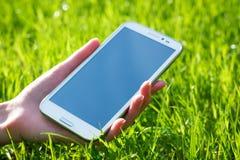 De Holdings Slimme Telefoon van de vrouwenhand op Groene Achtergrond royalty-vrije stock foto