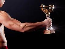 De holdings winnende kop van de mens royalty-vrije stock fotografie