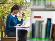 De holdingsappel van het meisje in bibliotheek Stock Foto
