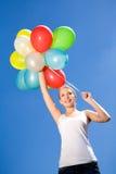 De holdingsballons van de vrouw tegen blauwe hemel Stock Afbeeldingen
