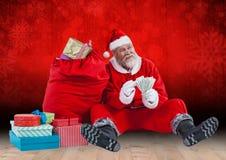 De holdingsbankbiljetten die van de Kerstman door giftzak zitten Royalty-vrije Stock Afbeeldingen