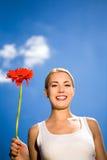De holdingsbloem van de vrouw tegen blauwe hemel stock foto's