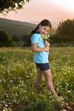 De holdingsbloemen van het meisje op gebied bij zonsondergang Stock Afbeeldingen