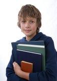 De holdingsboeken van de jongen stock foto