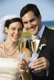 De holdingschampagne van de bruid en van de bruidegom. Stock Afbeeldingen