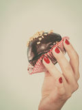 De holdingschocolade van de vrouwenhand cupcake ongeveer aan beet stock afbeelding