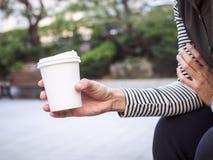 De holdingsdocument van de vrouwenhand Kop van koffie in Park Openlucht stock afbeeldingen