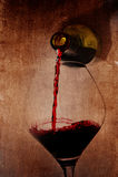 De holdingsfles die van de mensenhand rode wijn het vullen Glas op arty achtergrond gieten Stock Foto's