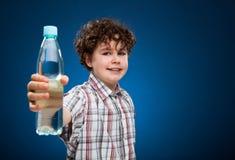 De holdingsfles van de jongen water Stock Foto