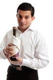 De holdingsfles van de kelner of van de bediende wijn stock foto