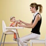 De holdingsfles van de moeder voor baby in highchair Stock Fotografie