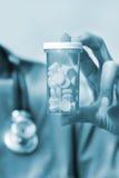 De holdingsfles van de verpleegster van pillen Royalty-vrije Stock Foto's
