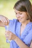 De holdingsfles van het vrouwenclose-up water Royalty-vrije Stock Foto's