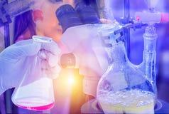 De de holdingsfles van de wetenschapperhand met distillatie met het dalen trechters wordt geplaatst scheidt de componentensubstan stock afbeeldingen