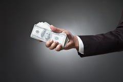 De holdingsgeld van de zakenmanhand op donkere achtergrond Stock Afbeelding