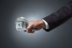 De holdingsgeld van de zakenmanhand op donkere achtergrond Stock Foto