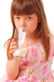 De holdingsglas van het meisje melk stock afbeelding