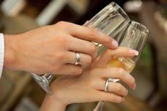 De holdingsglazen van de bruid en van de bruidegom Stock Fotografie