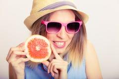 De holdingsgrapefruit van het de zomermeisje Stock Foto's