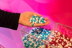 De holdingsgroep van de vrouwenhand blauwe en witte capsulegeneesmiddelen Royalty-vrije Stock Foto