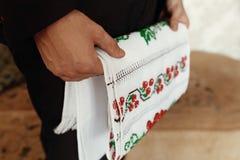 De holdingshanddoek van de mensenholding met Oekraïens borduurwerk vóór weddi stock afbeelding