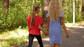 De holdingshanden die van het tienersmeisje in de achtermening van het de zomerpark lopen Twee meisjes die op parkweg bij de zome stock videobeelden