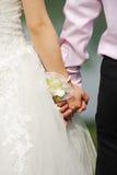 De holdingshanden van de bruid en van de Bruidegom Stock Fotografie