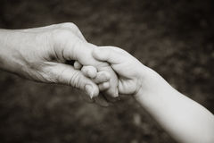 De holdingshanden van de grootouder en van het kleinkind stock foto