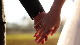 De holdingshanden van het huwelijkspaar op zonsondergangachtergrond stock videobeelden