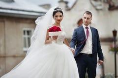 De holdingshanden van het jonggehuwde romantische paar en het stellen in oude europea Royalty-vrije Stock Foto