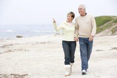 De holdingshanden van het paar bij strand het glimlachen Stock Foto