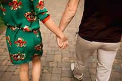 De holdingshanden van het paar en het lopen in een park Stock Fotografie