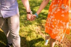 De holdingshanden van het paar en het lopen in een park Stock Afbeelding