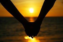 De holdingshanden van het paar op het strand Stock Fotografie