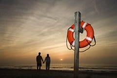 De holdingshanden van het paar op strand Stock Afbeeldingen