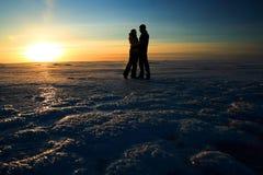 De holdingshanden van het paar tegen zonsondergang op bevroren overzees Royalty-vrije Stock Foto's
