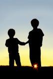 De Holdingshanden van silhouet Jonge Kinderen bij Zonsondergang Royalty-vrije Stock Afbeeldingen