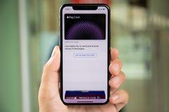 De holdingsiphone X van de mensenhand met Apple betaalt Contant geld royalty-vrije stock afbeeldingen