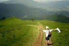 De holdingskaart van de mensenreiziger en het lopen tot bovenkant van zonnige heuvel op bac Stock Foto's