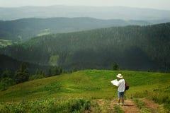 De holdingskaart van de mensenreiziger en het onderzoeken bovenop zonnige heuvel op B Stock Foto's