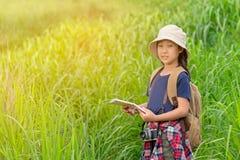 De holdingskaarten van het kinderen Aziatische meisje en reisrugzakken die in het groene bos lopen stock foto