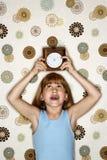 De holdingsklok van het meisje lucht. Stock Foto's