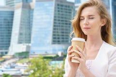 De holdingskoffie van het bedrijfsvrouwenblonde in openlucht op stadsachtergrond stock foto